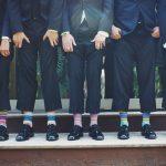 Üzletemberek állnak egy sorban nadrágjukat felhúzva, zoknijukat mutatva