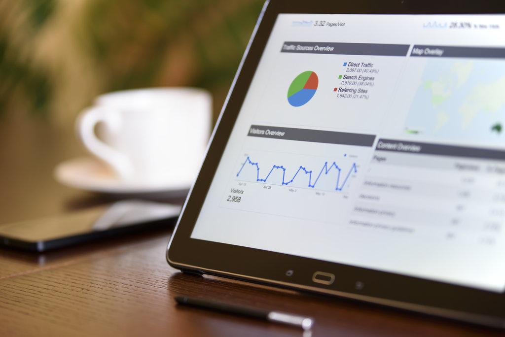 Analítikus adatok, grafikonok egy asztalon lévő táblagépen