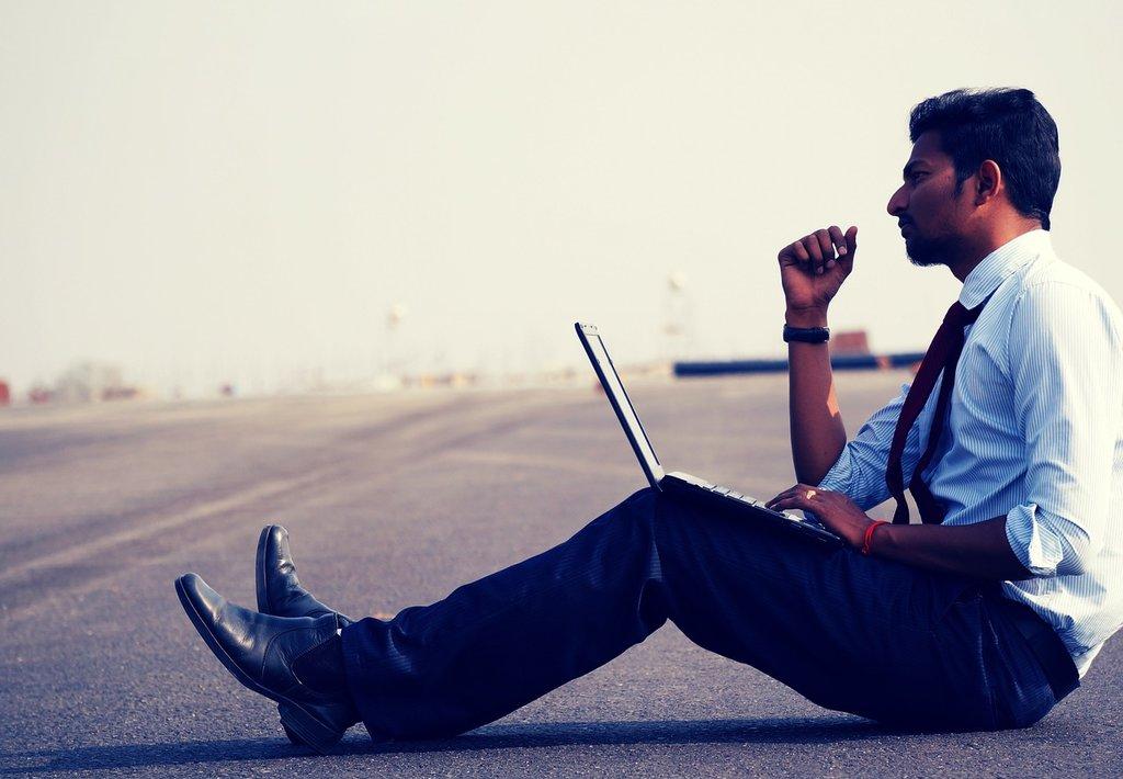 Marketinges ül az aszfalton laptopjával