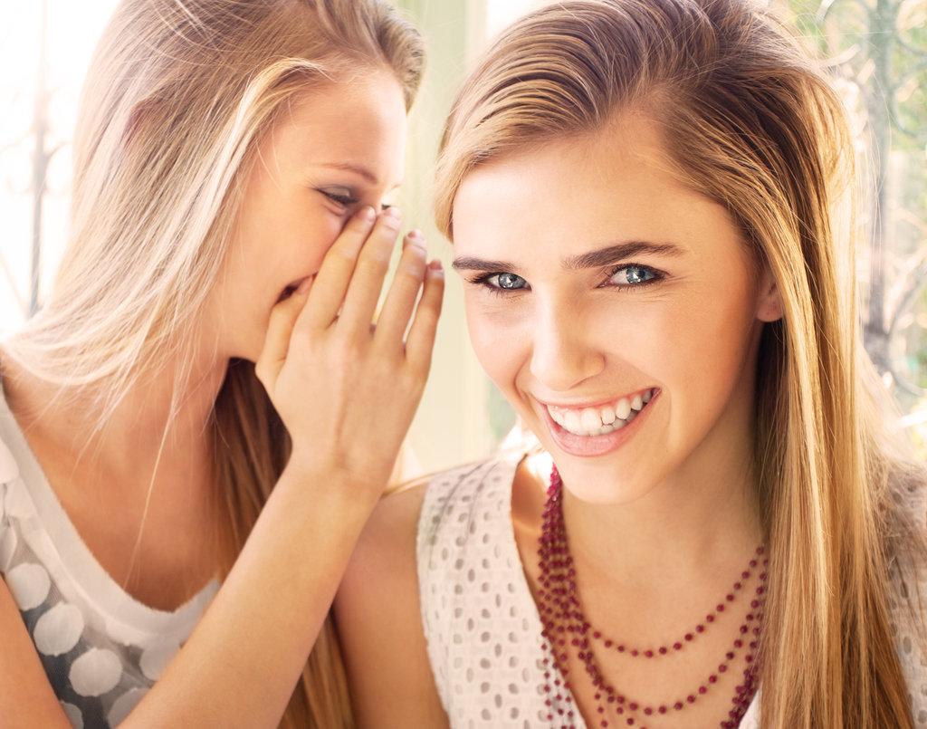 Fiatal lány súg valamit barátnője fülébe